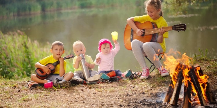 four children sit by a lake and a fire singing camp songs
