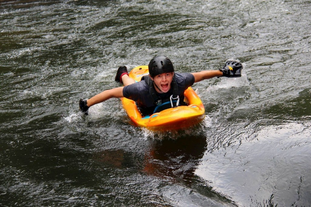a man smiling and paddling down a river
