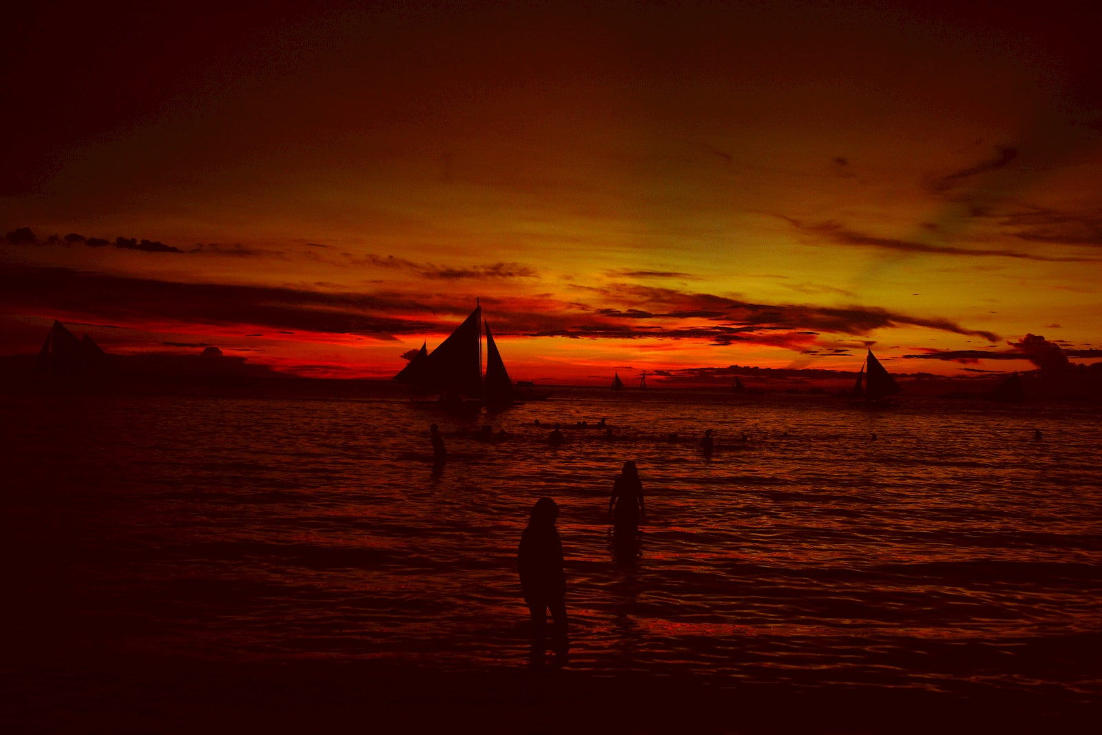 People on the beach overlooking sailboats at sunset.