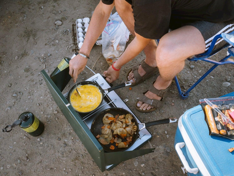 Camper cooking breakfast on a 2 burner stove.