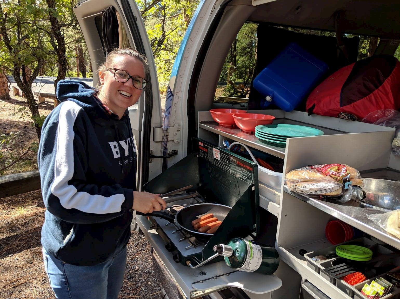 Women cooking in her van kitchen.