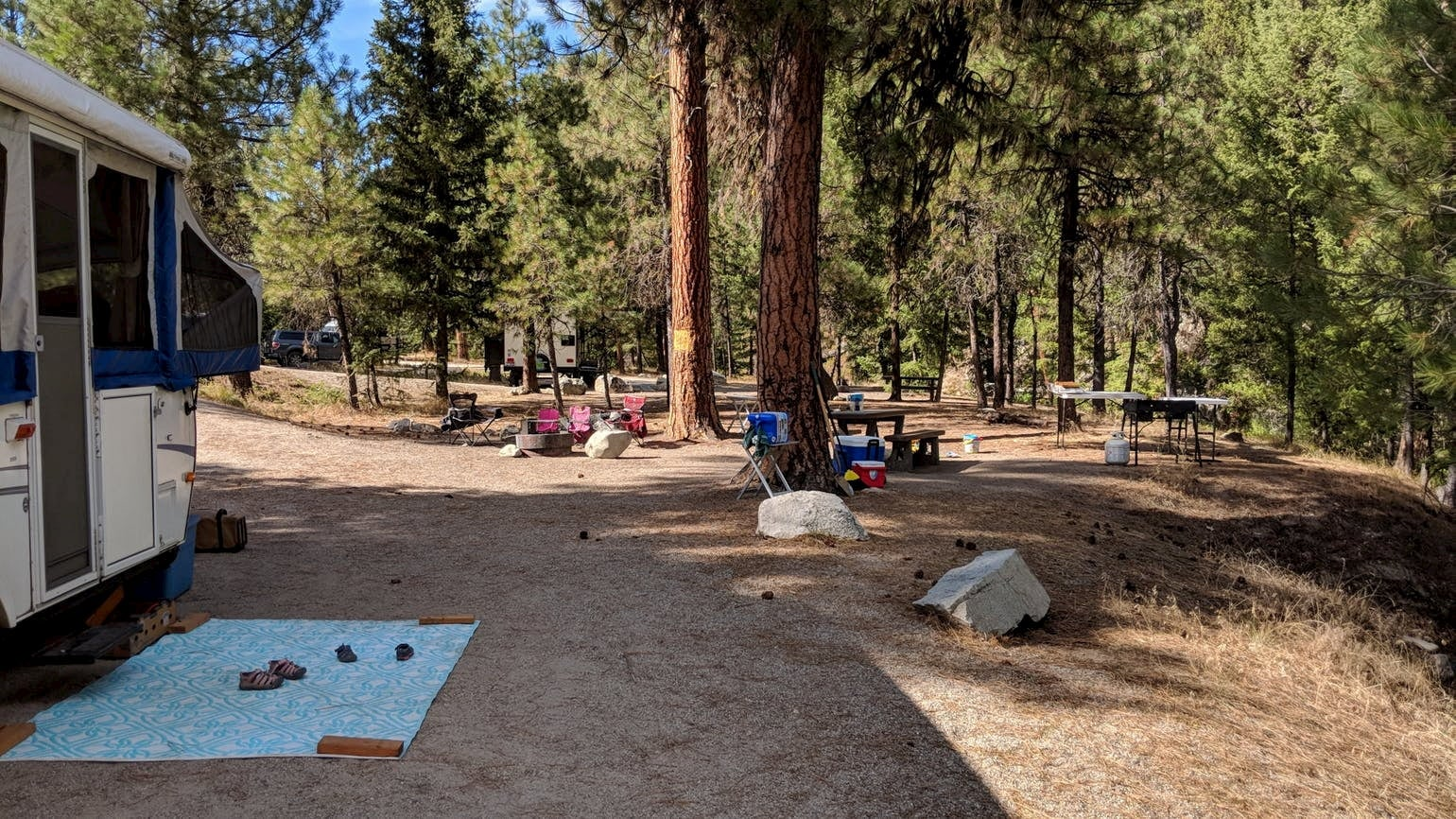 Wooded campground with dispersed campers and camp chairs.