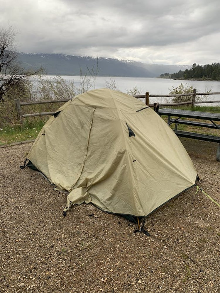 Tan tent beside a lake with snow capped mountains in the background.