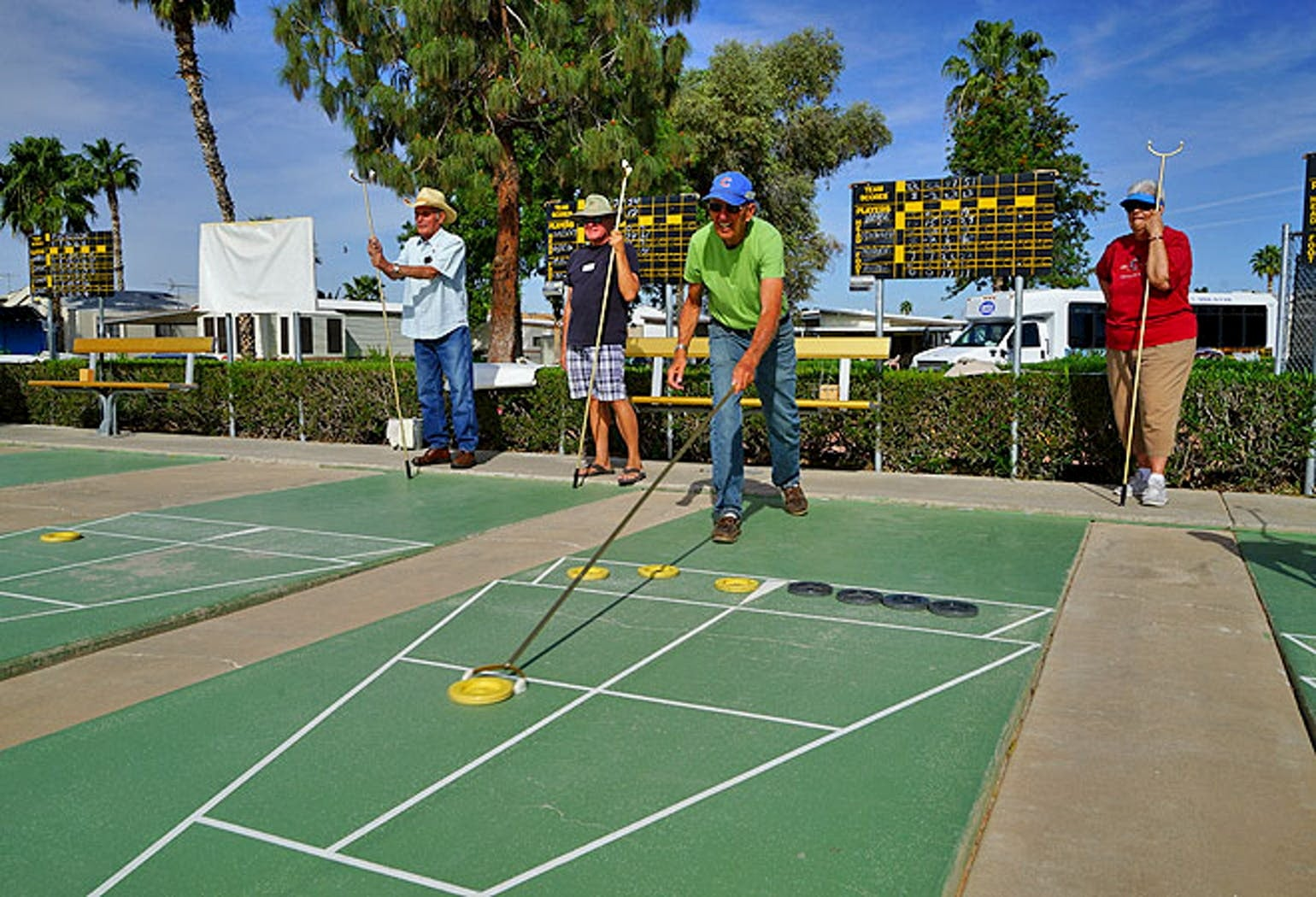 Elderly retirees playing shuffleboard outdoors surrounded by palm trees.