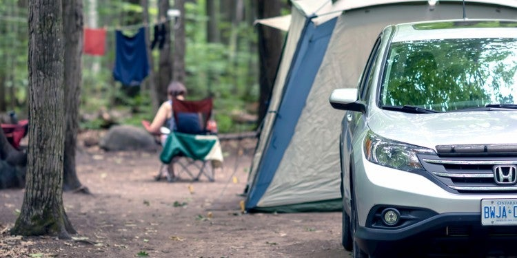 Car parked in front of campsite with tent and clothesline.