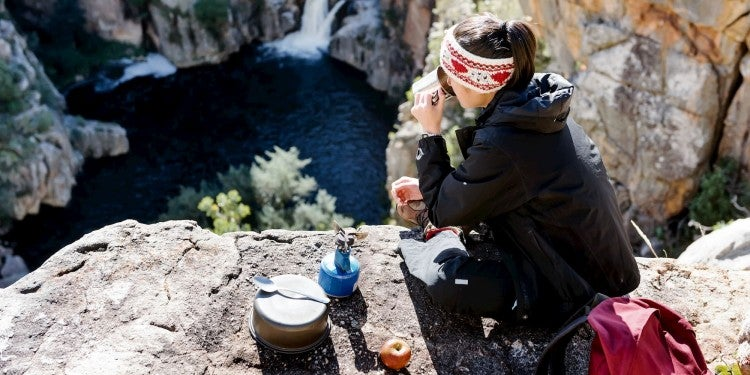 Backpacker cooking on a stove over scenic overlook.