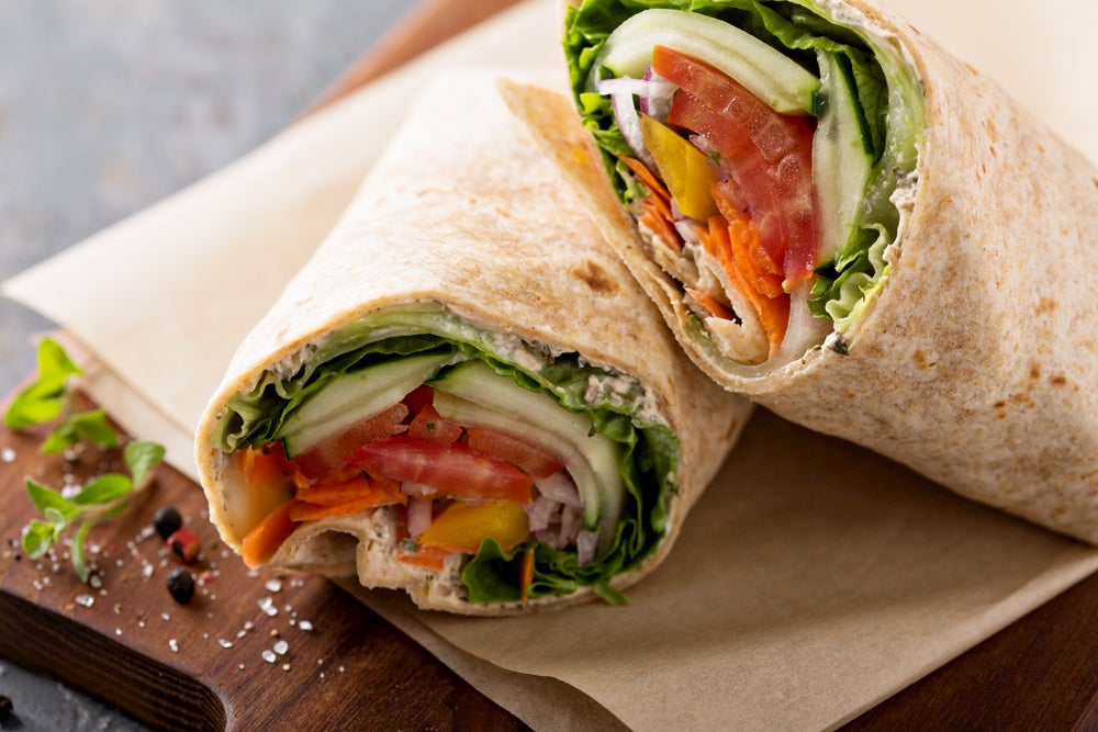 Veggie wrap on a wooden platter.