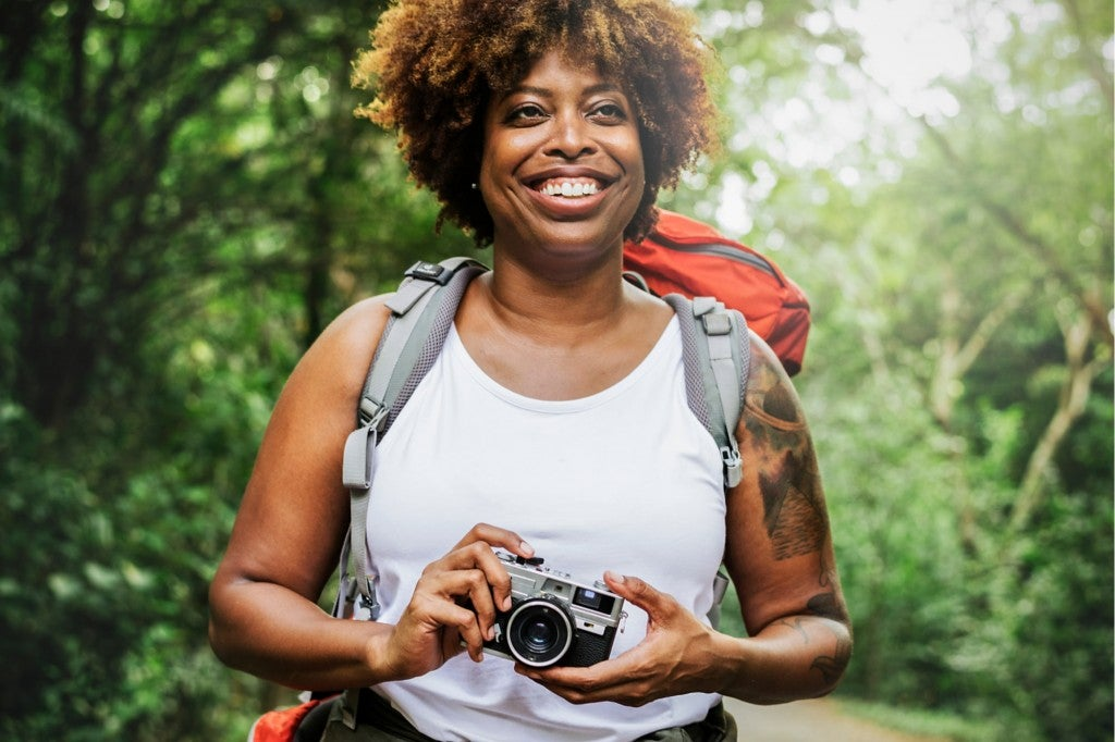 a woman holding a camera with a hiking tattoo