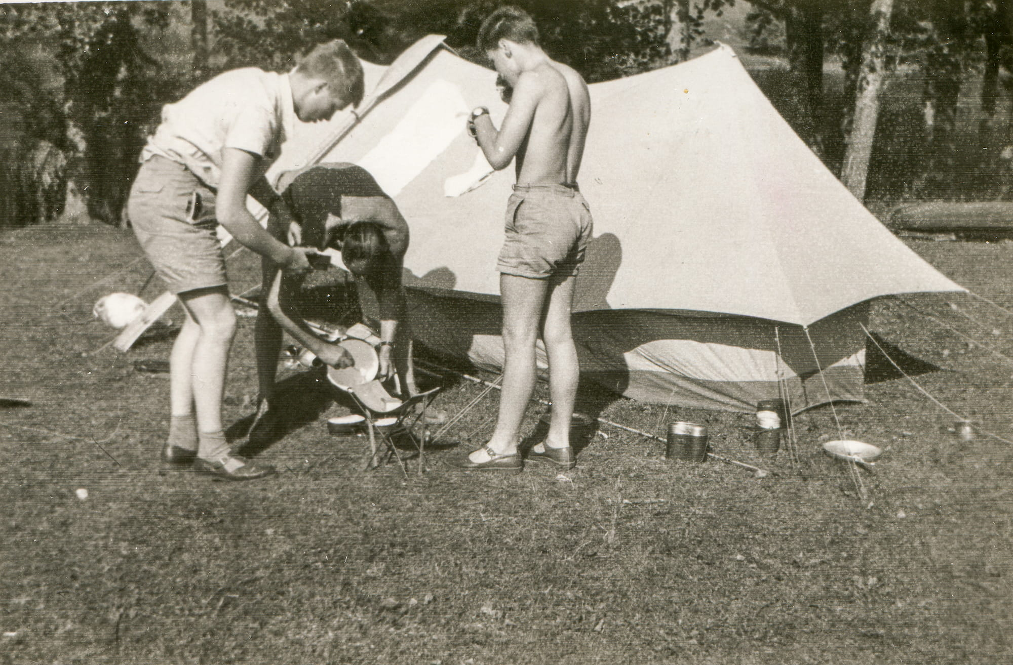 3 young men setting up a stove at a campsite.
