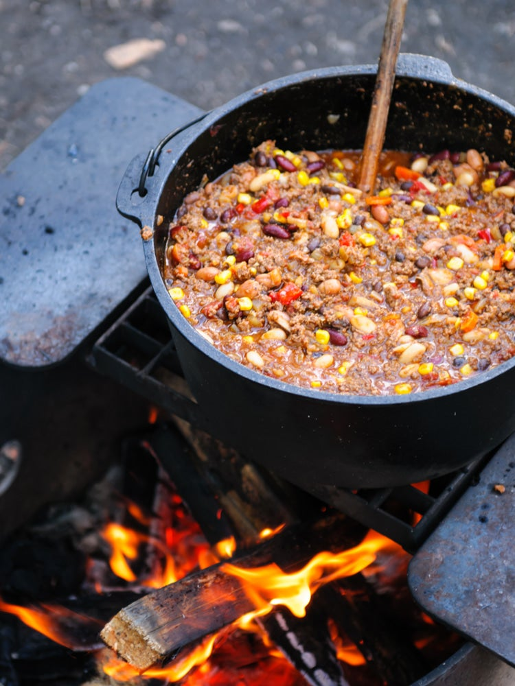 a pot of chili over a campfire