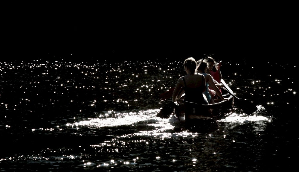 Group of women paddling a canoe under the moonlight.