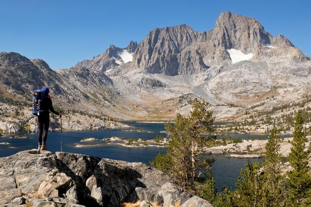Backpacker of looking a lake in the Sierra Nevada range.