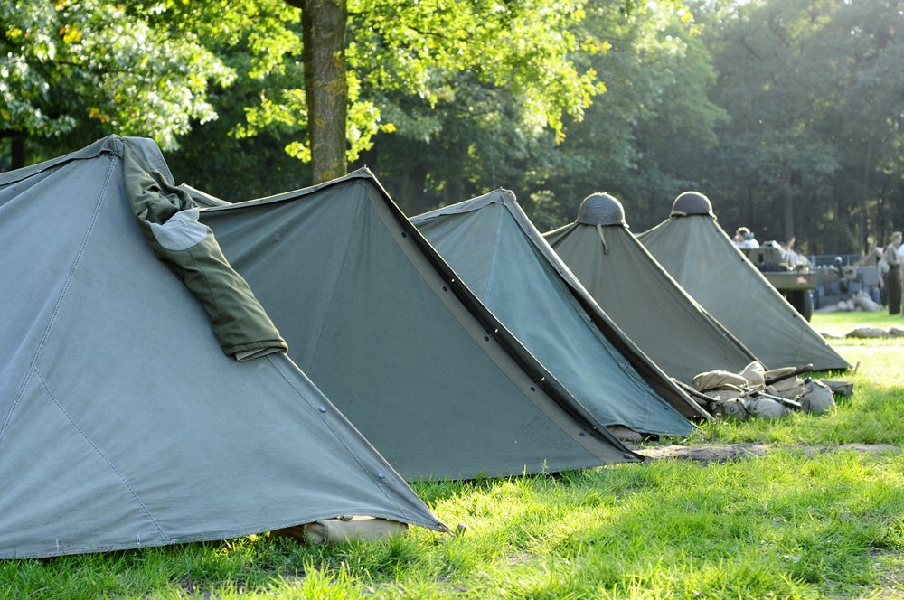 Military campsite with green canvas tents.