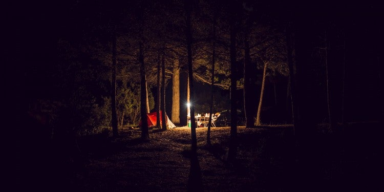 Lantern lighting up a campsite in the woods at night.
