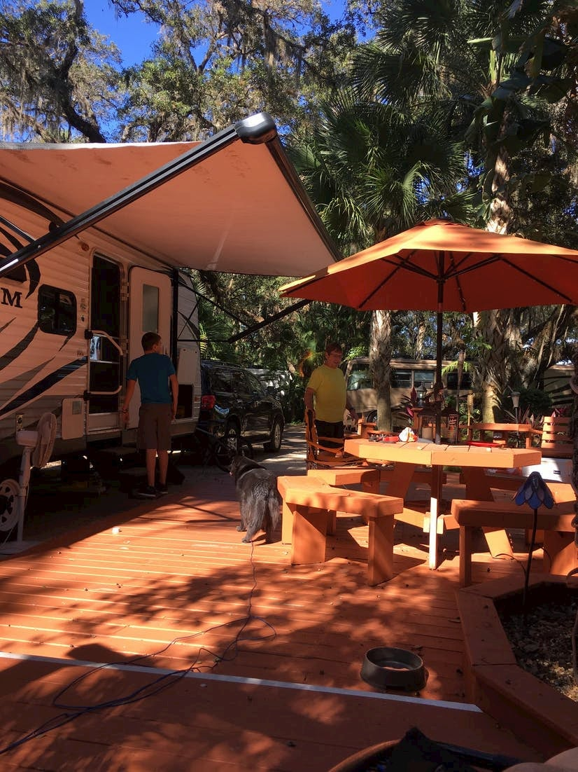 RV with awning parked beside wooden deck.