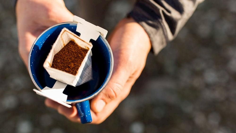 Aerial image of person holding coffee filter within a camp mug.