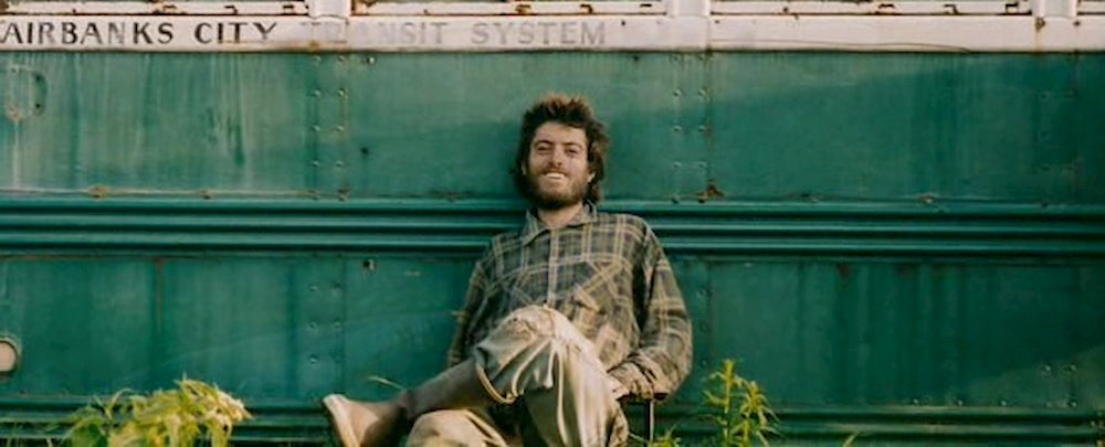 Scruffy guy leaning against a green bus.
