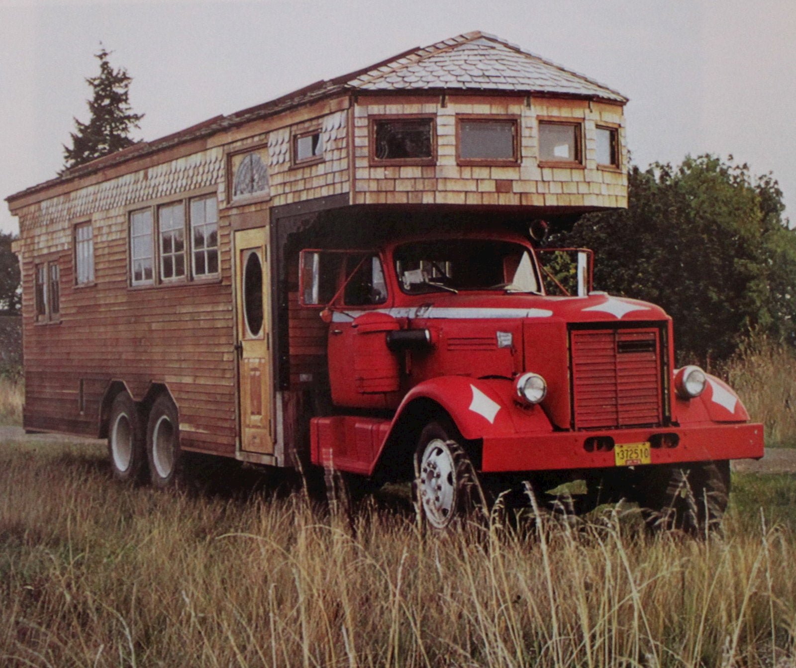 Bus with wooden built out structure parked in a field.