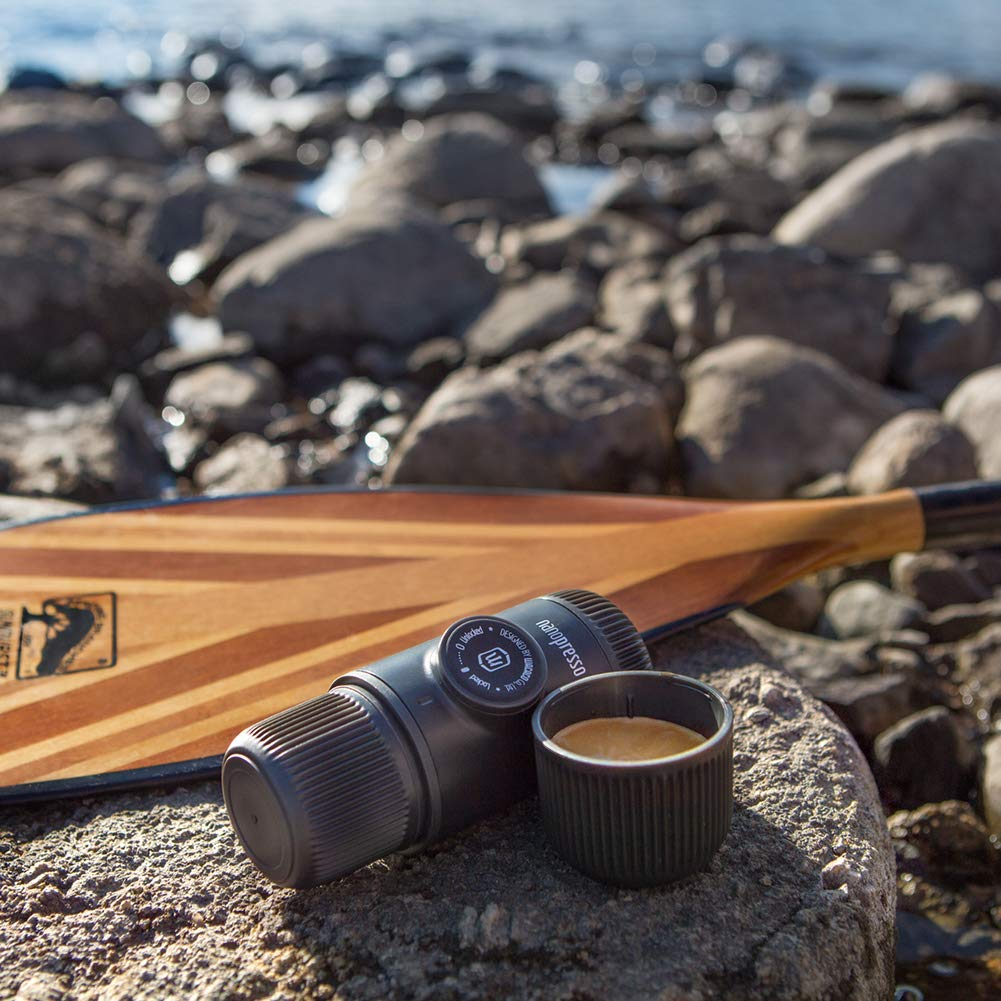 Cup of coffee and black coffee maker beside a wooden paddle on rocks by a seashore.