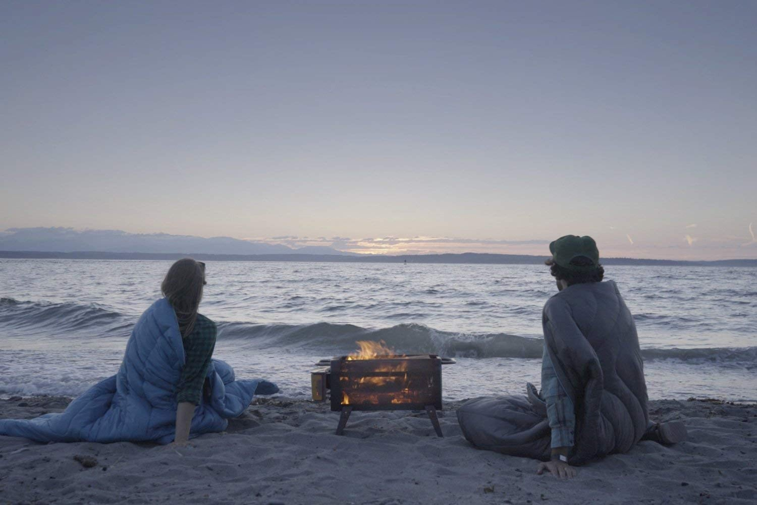Couple sitting in blankets on the beach beside a fire pit.
