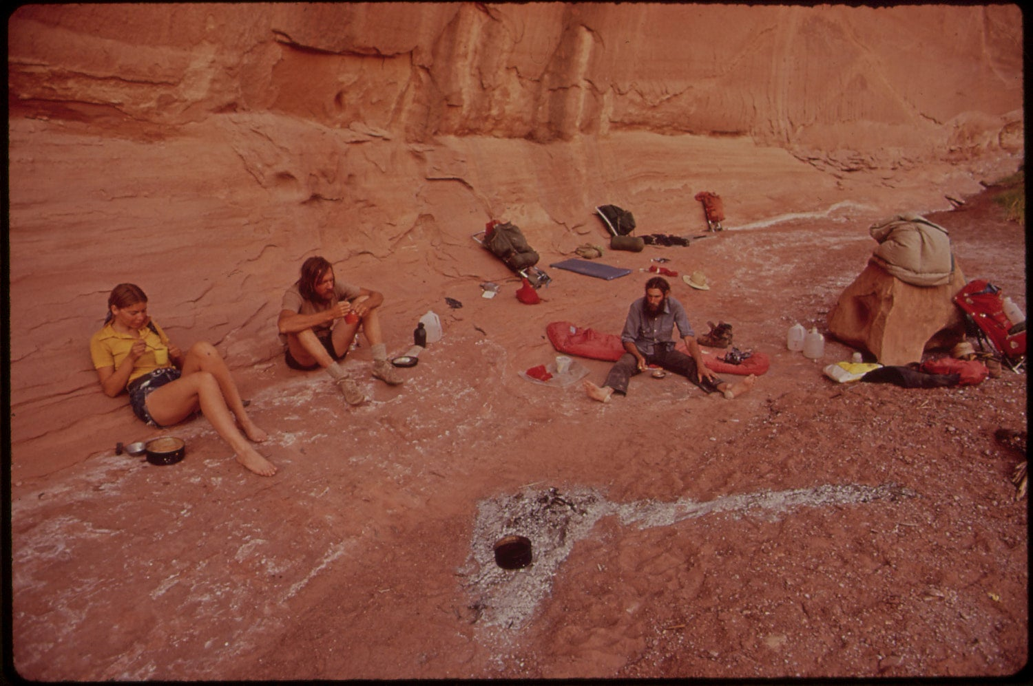 backpackers taking a break with their gear spread around in the maze at canyonlands
