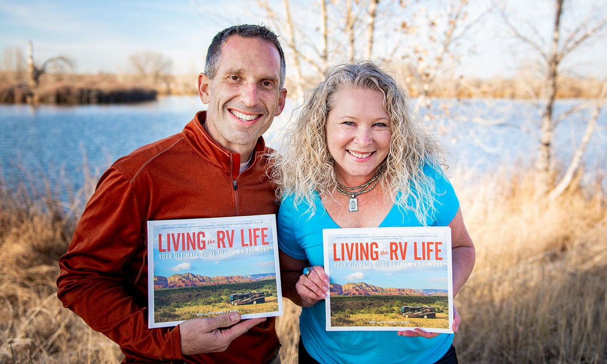 Authors of Living the RV Life holding the published book outside.