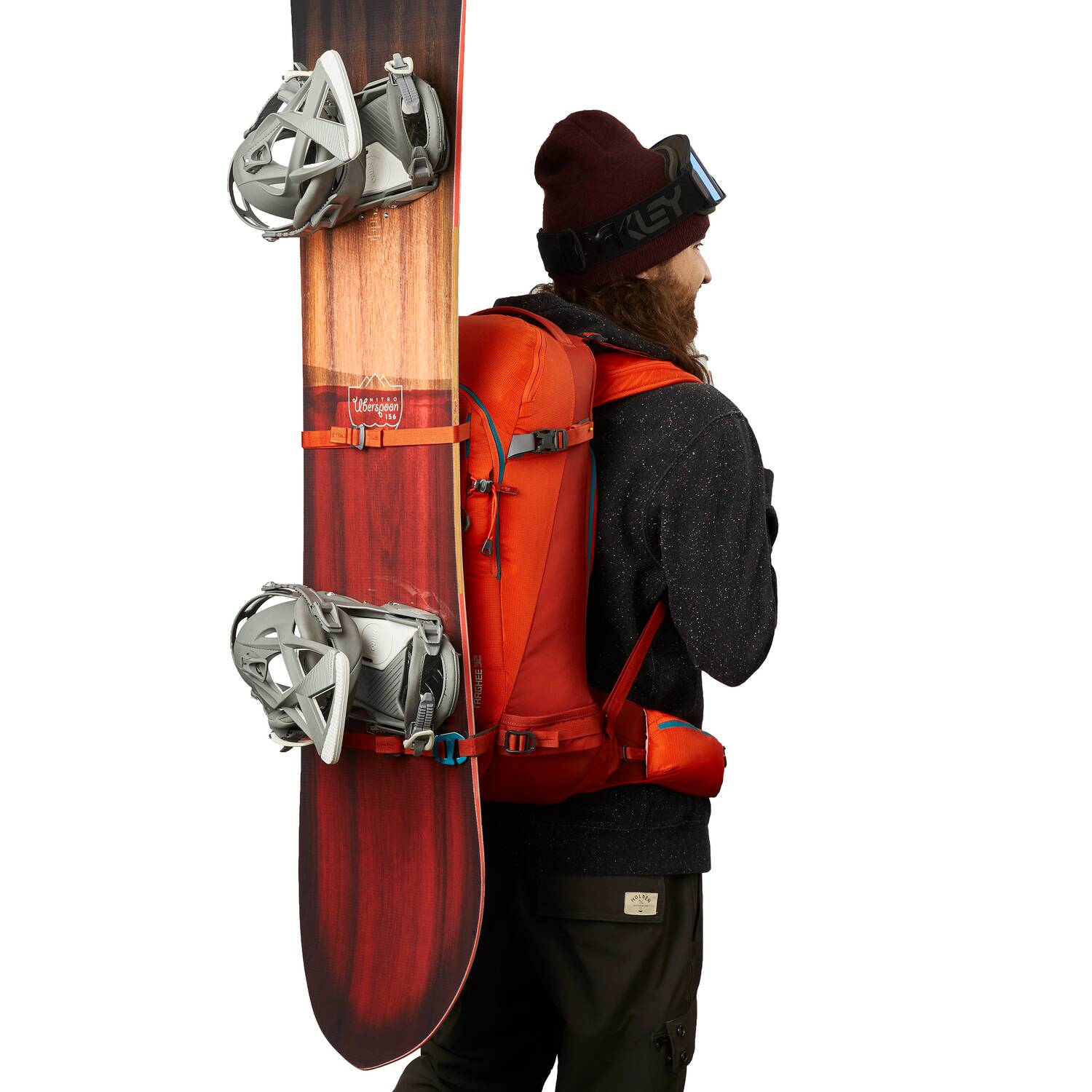 Man wearing orange backpack with snowboard attached to it.