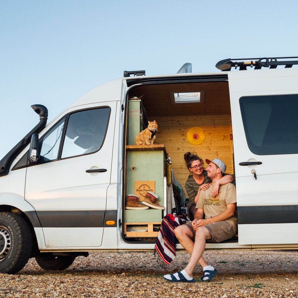 Couple embracing inside their sprinter van.