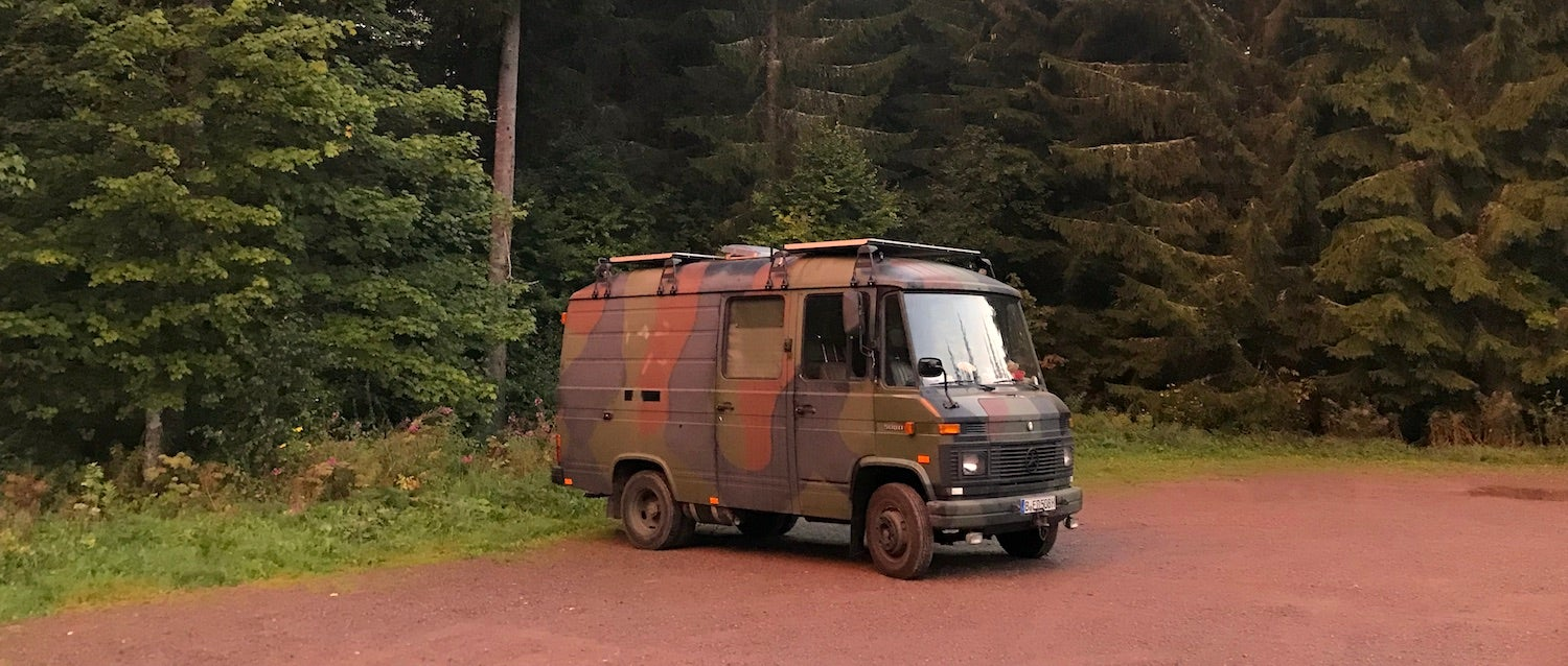 Camouflage painted converted van parked beside a forest.
