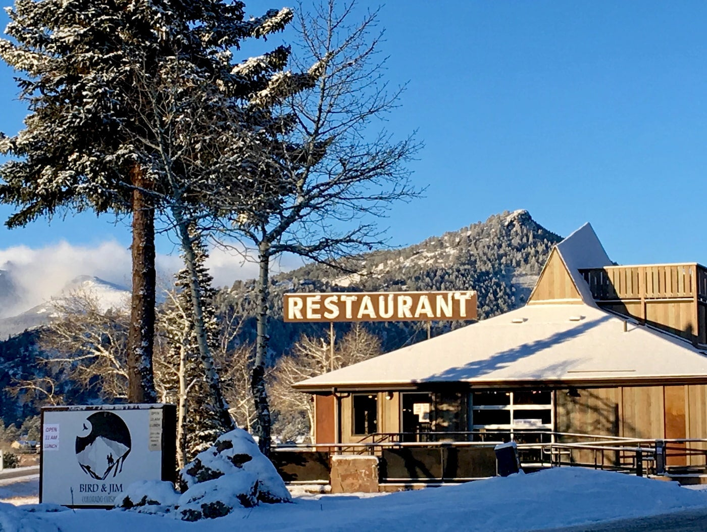 Snow covered wooden barn style restaurant with large painted sign.