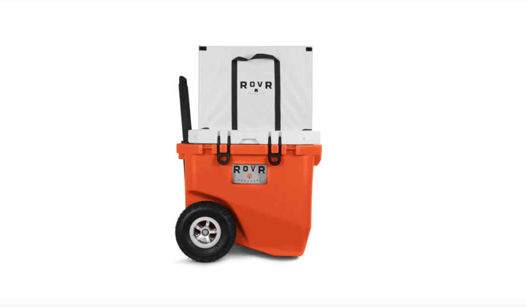 Orange rovr cooler with all terrain wheels and pop up handle.