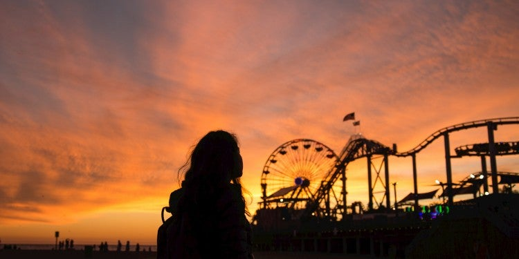 Silhouette of a woman at sunset on a pier with a ferris wheel.