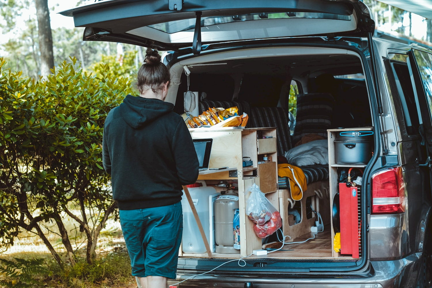 Van lifer using their laptop in their built out van kitchen.