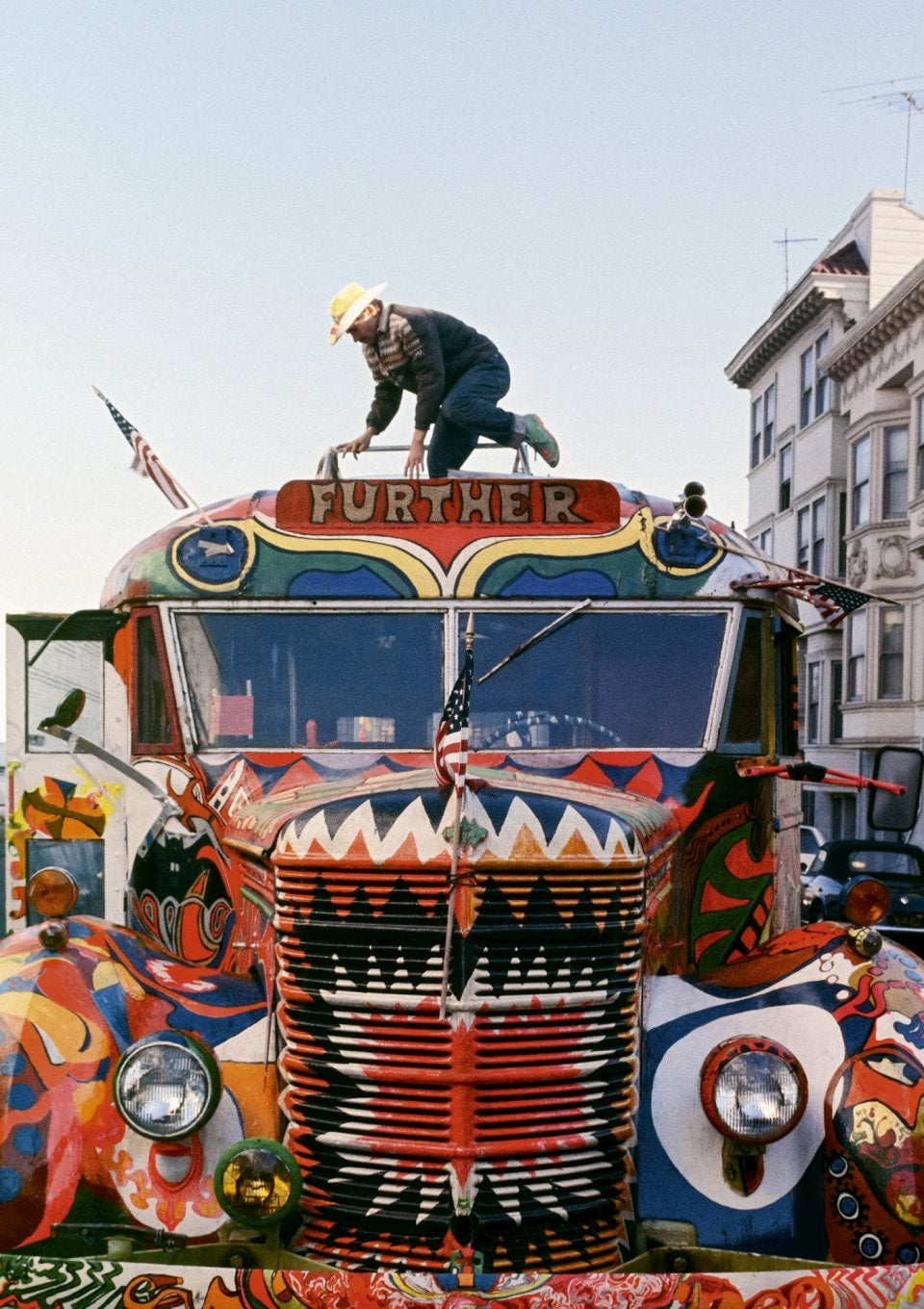 Man standing on top of an eclectic painted bus.