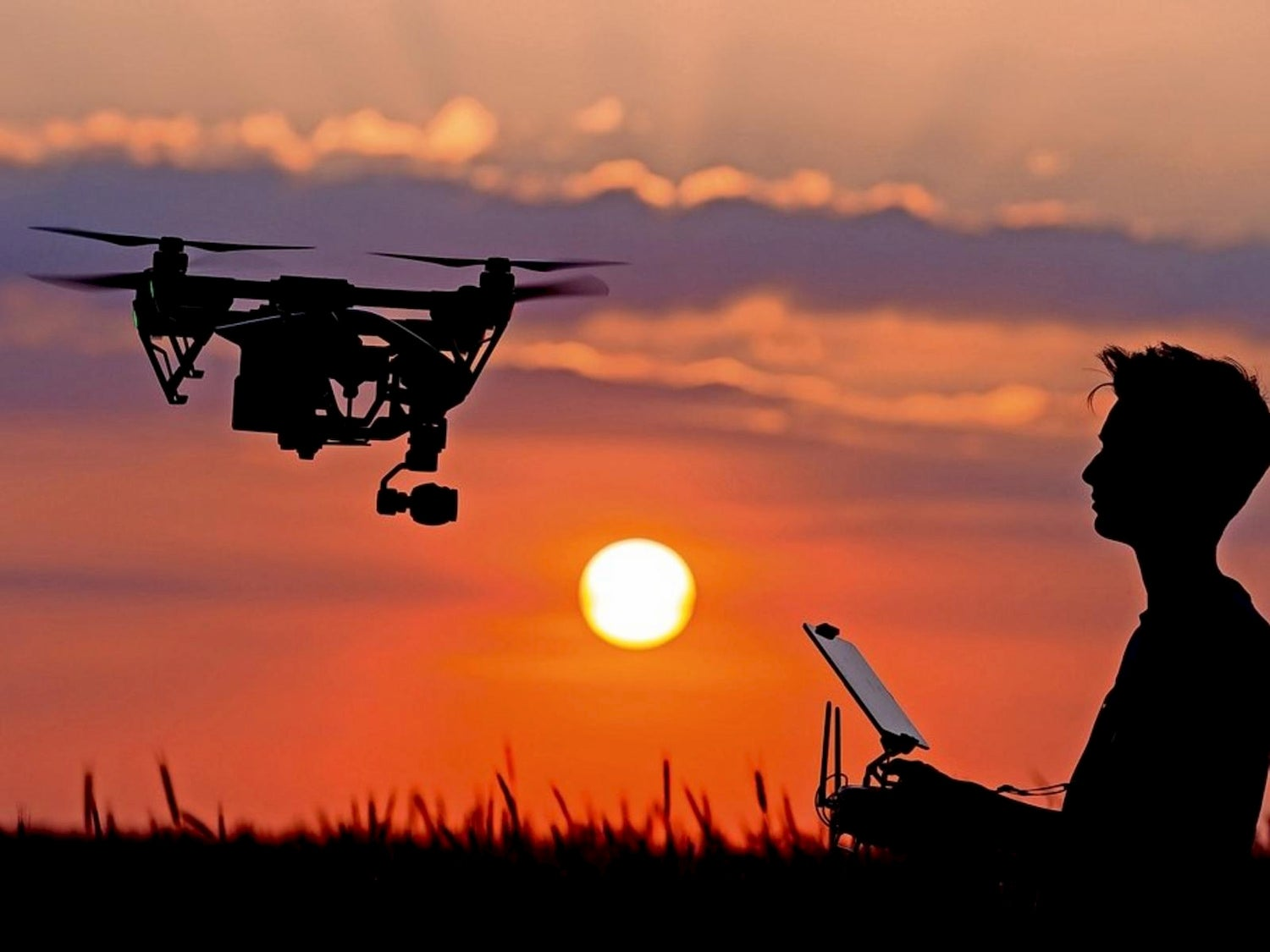 silhouette of person flying drone in sunset