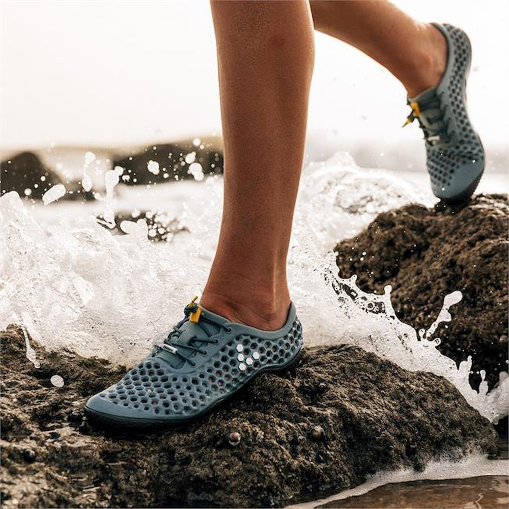 Person with blue porous water shoes walking on rocks in water.