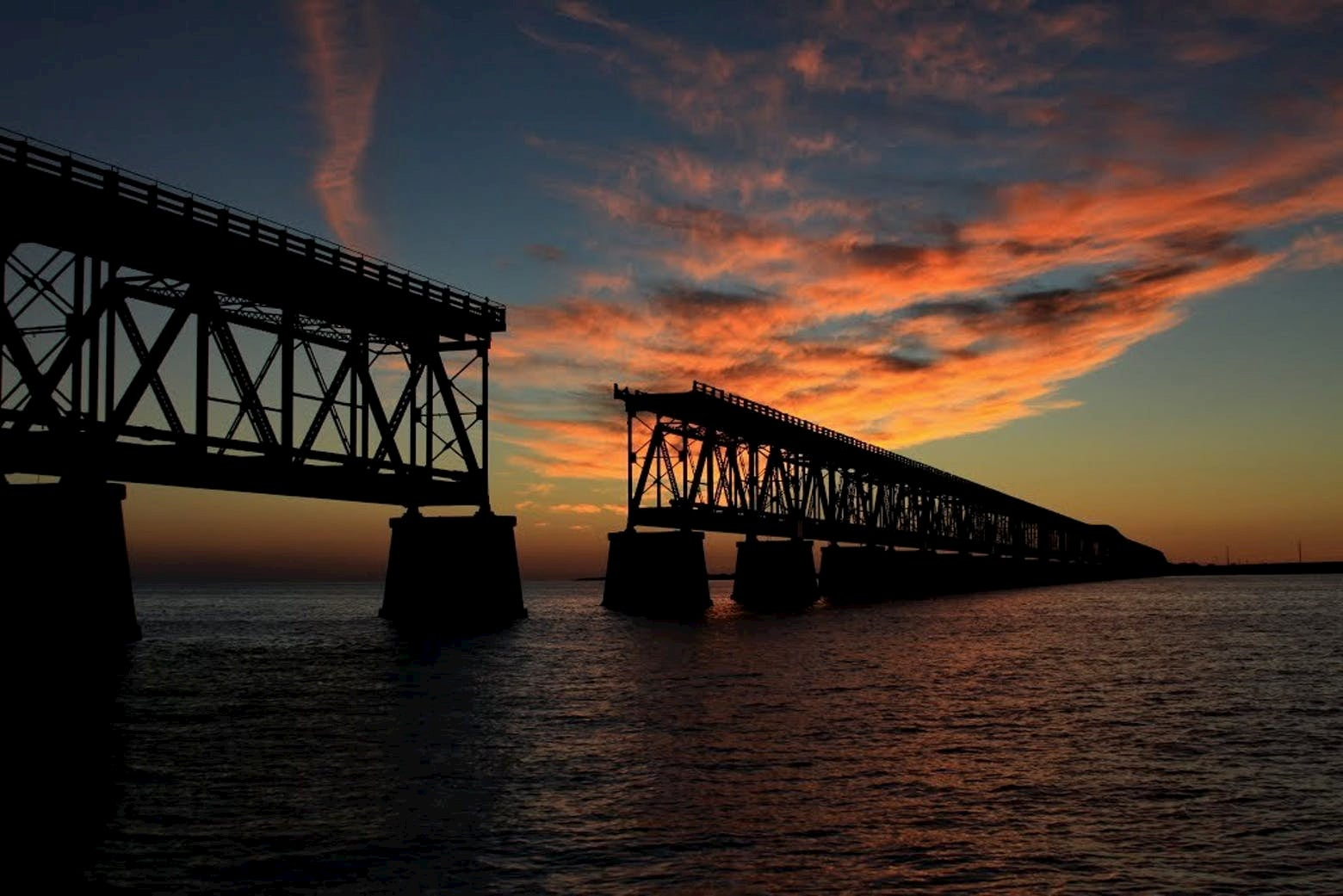 Silhouette of a bridge over the ocean at sunset with pink clouds.