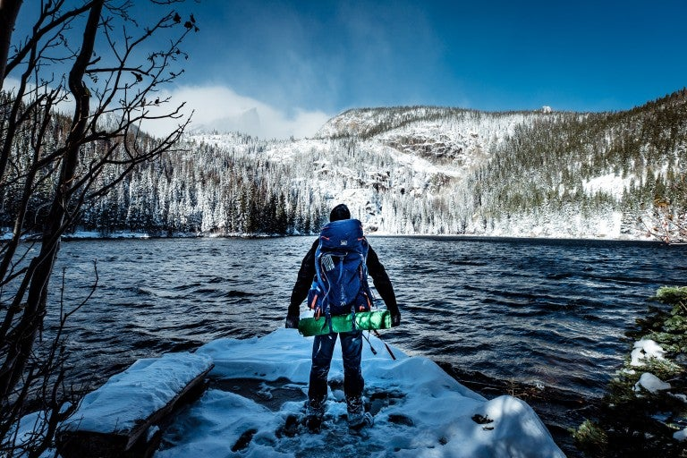 Backpacker hiking through Rocky Mountain National Park in the winter.