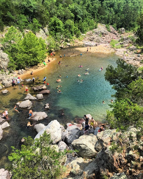 overhead shot of natural pool filled with swimmers