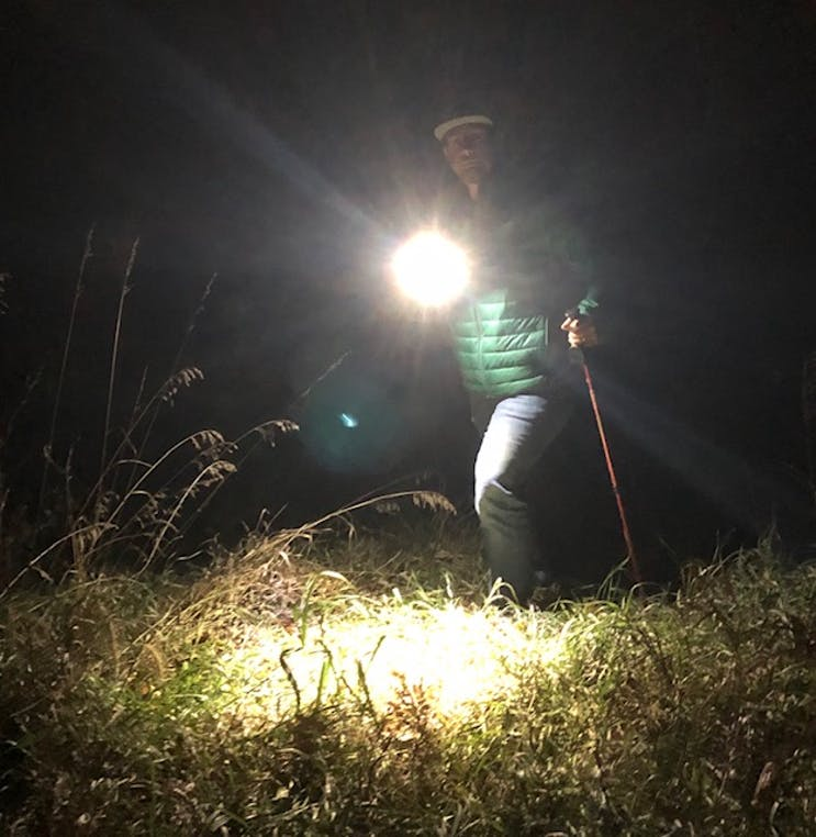 a man holding a flashlight in the woods