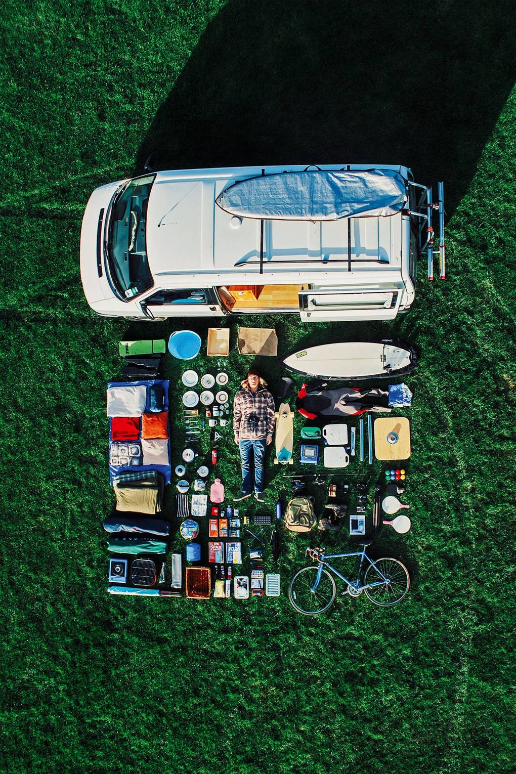 Flat lay on the grass of man and all of his possessions outside of his van.