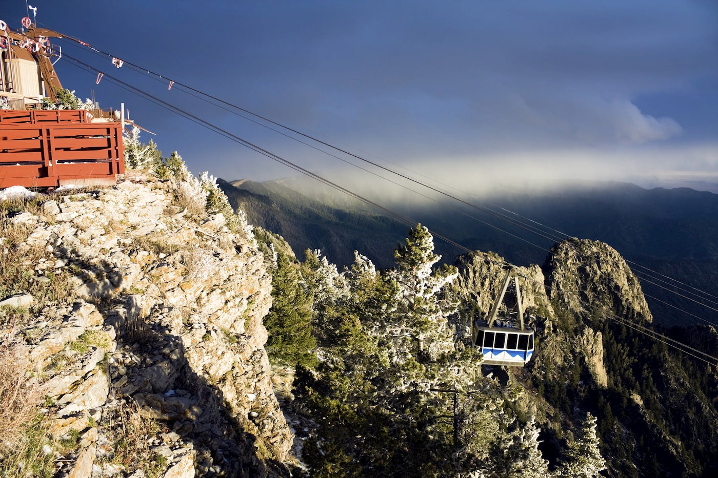 Tram on wire cables in the mountains with dark cloud in the background.