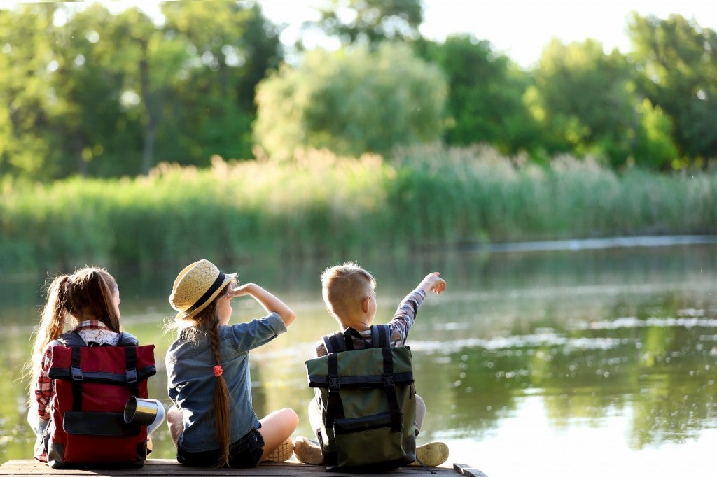 three kids overlooking a river wearing outdoor gear