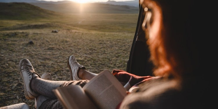 Women reading out of the backside of a van at sunset.