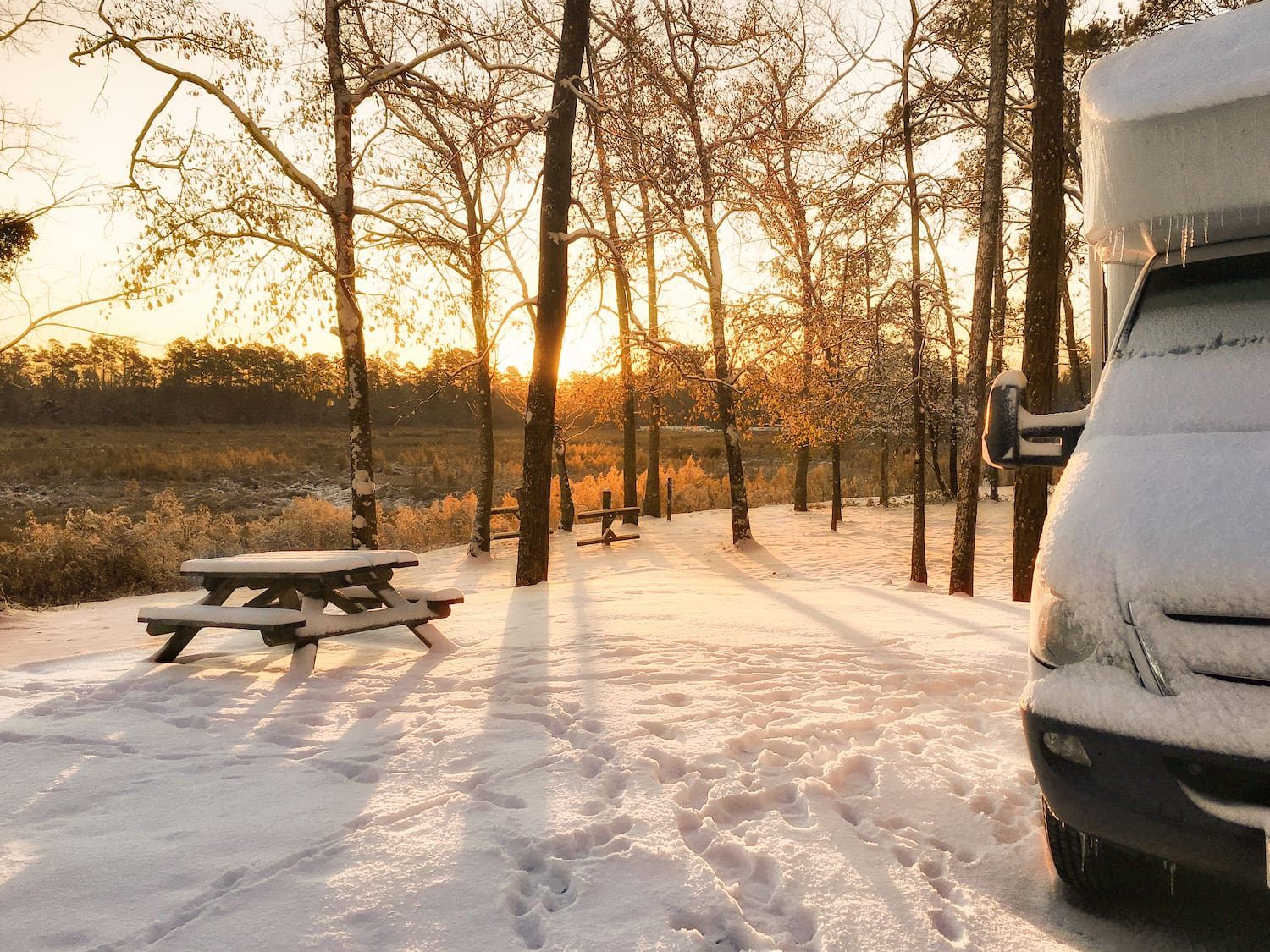frozen RV camper parked at sunrise with picnic table in the background
