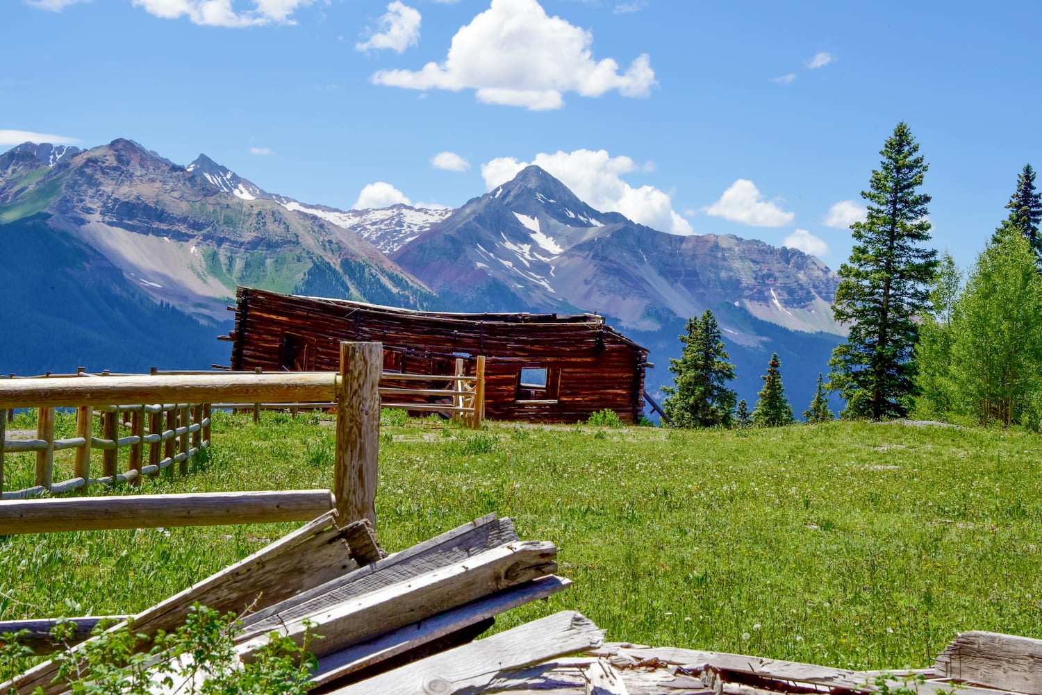 green grass, wood fence, abandoned cabin and mountain peaks in the background