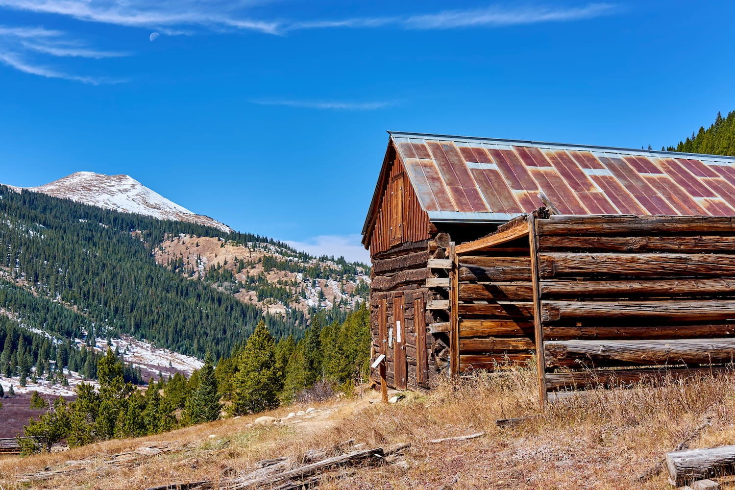 abandoned cabin with mountain peak in the background