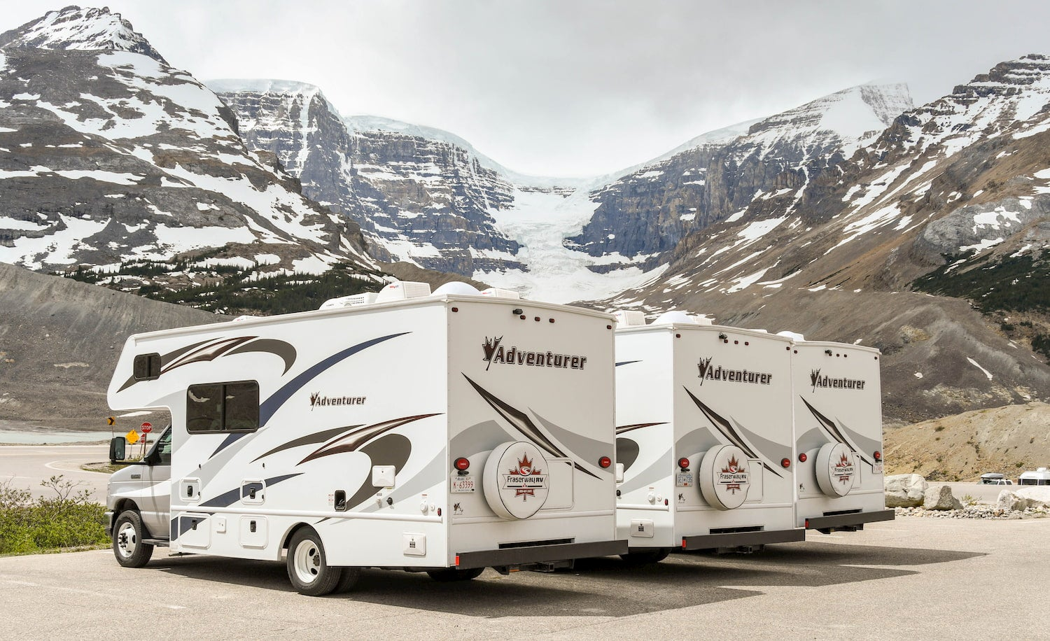 row of RVs infront of snowcapped mountains