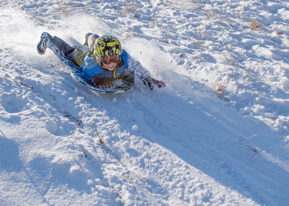 Young boy sledding down a snow covered hill.