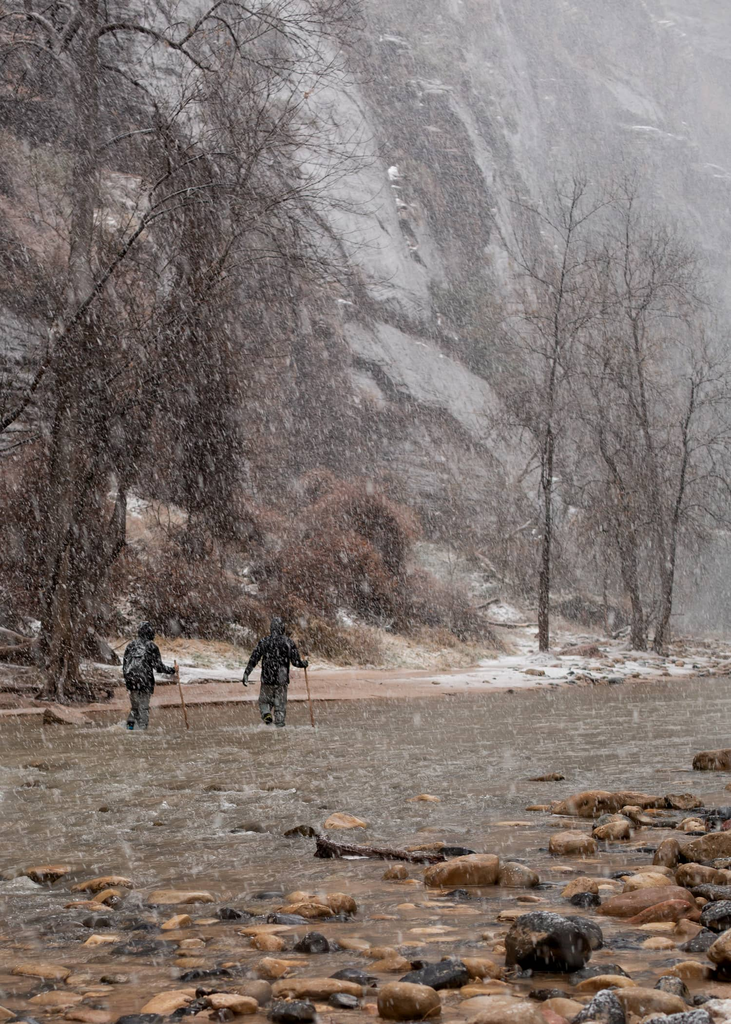 Two men make their way upstream in the Narrows in Zion national park on a cold snowy winter day.